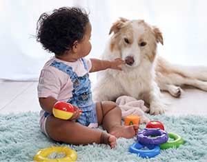 baby sitting with dog in living room